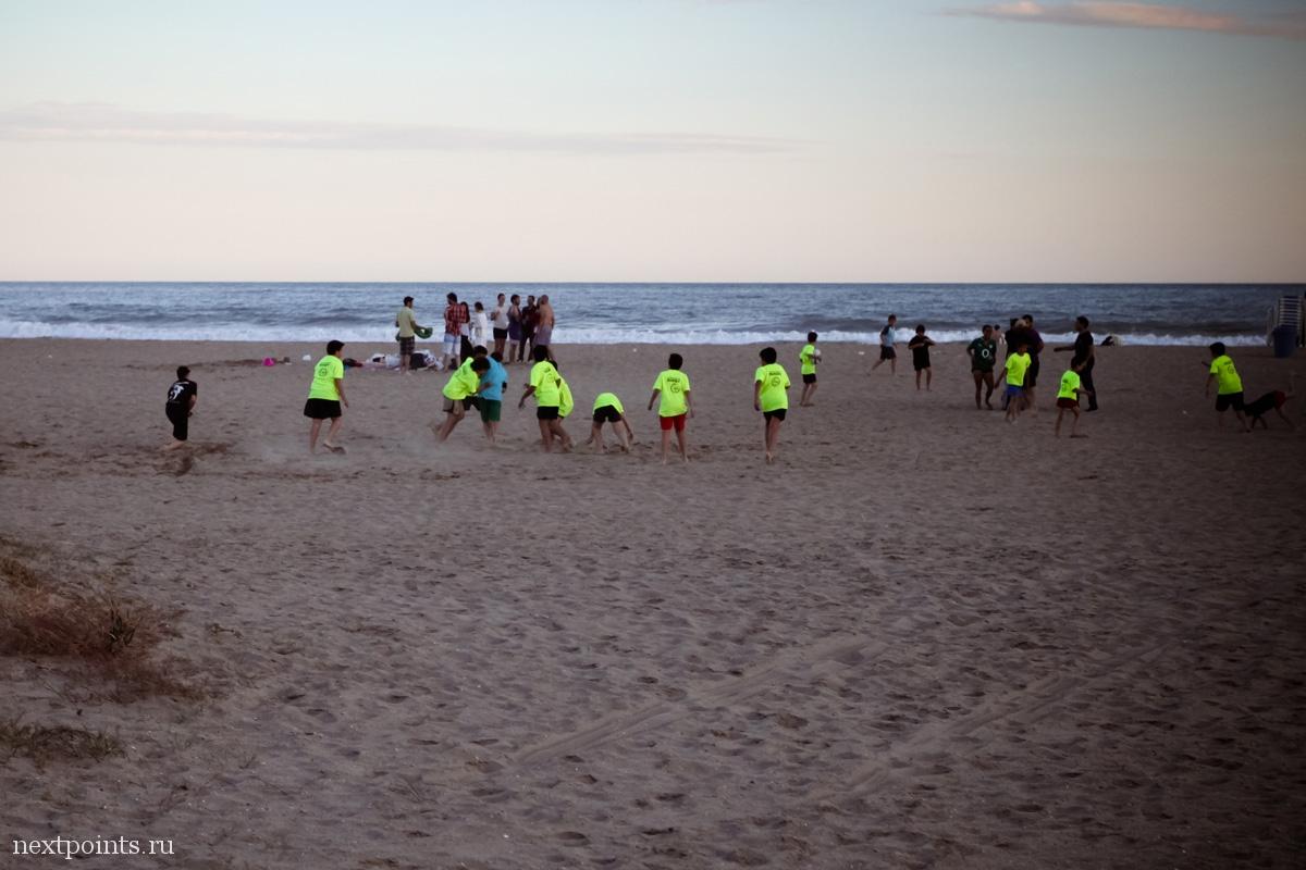 На пляже можно понаблюдать за молодыми футболистами, одетыми в цветастые командные футболки.