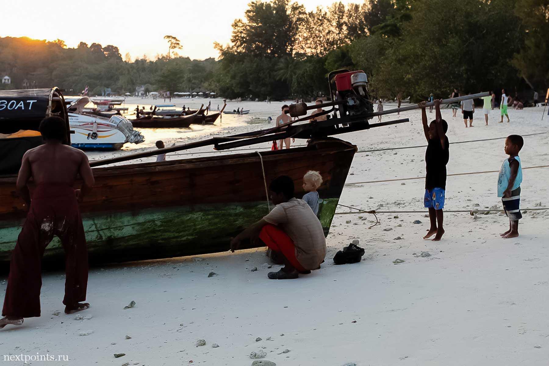 Рыбаки вынимают лодку вечером на Ко Липе