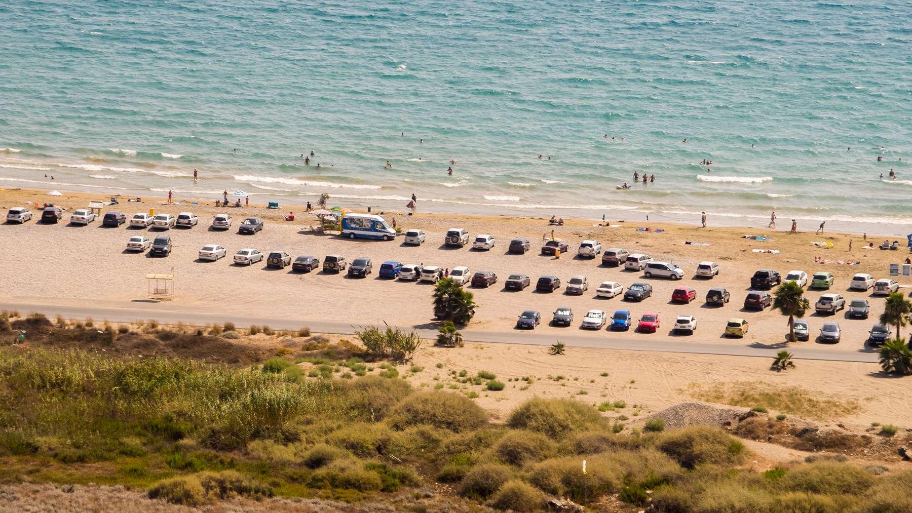 Отдыхающие люди и их машины на пляже Курион (Coureon beach)
