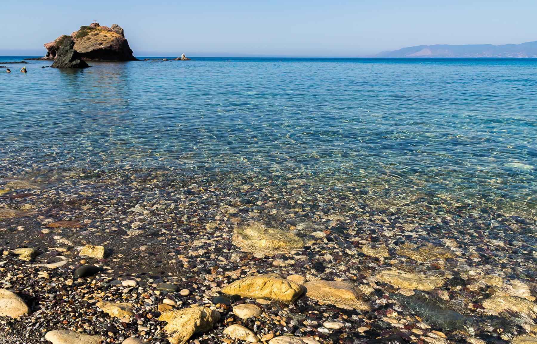 Каменистый, но мягкий заход в синее море Акамаса