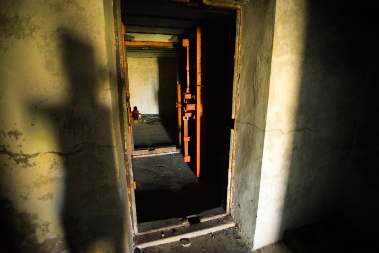 Ряд массивных железных дверей в помещениях без окон, похожих на матрешку