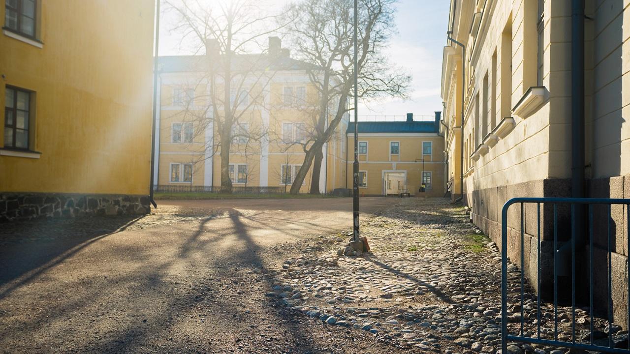 Солнце освещает дорогу между домов