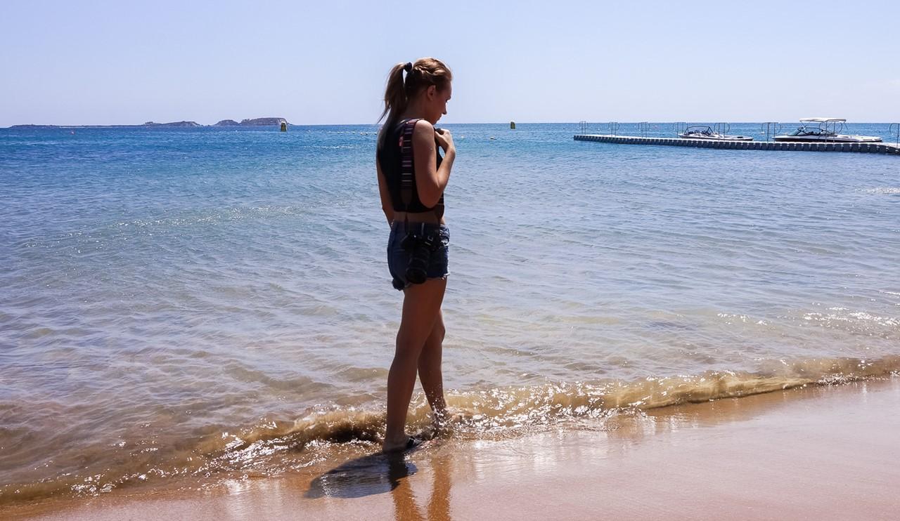 Приятный красный песок пляжа Кси (Xi)