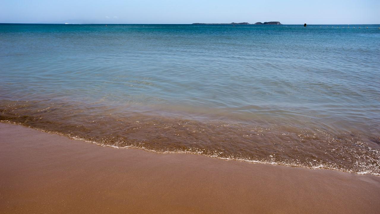 Красно-оранжевый песок на пляже Кси (Xi)
