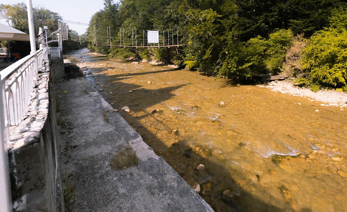Пешеходный мост через реку около отеля Гуамка